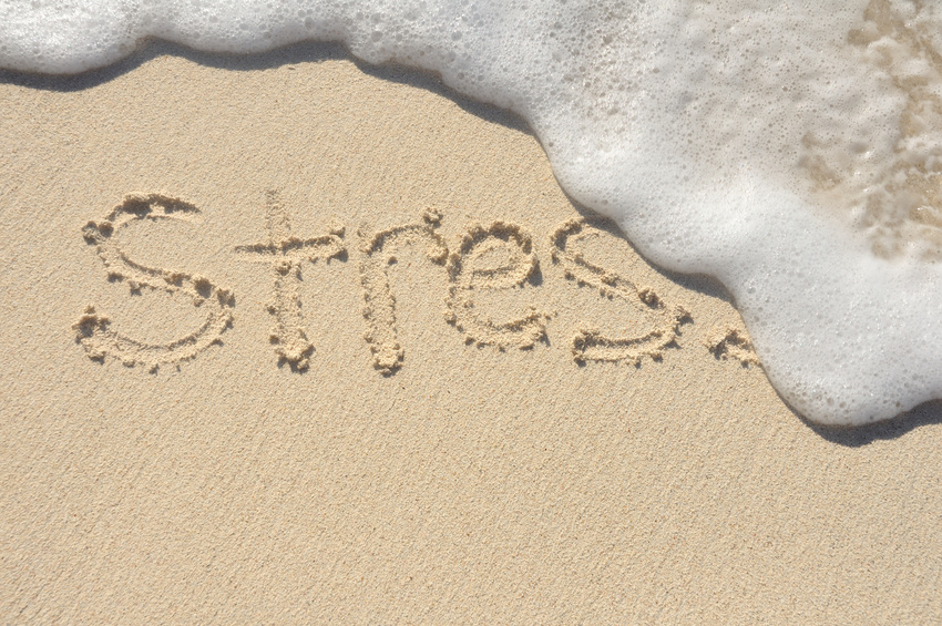 Releiving Stress, the Word Stress Being Washed Away by a Wave on a Beach